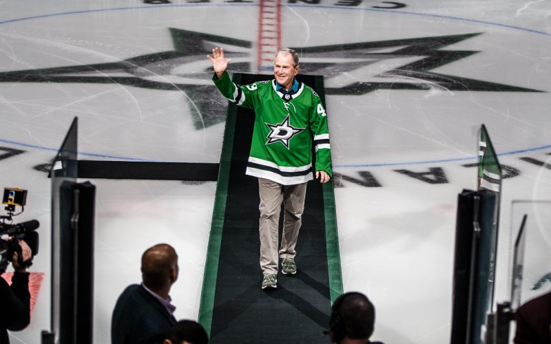 George W Bush in a Dallas Stars jersey, walking back after dropping the ceremonial puck before the game.